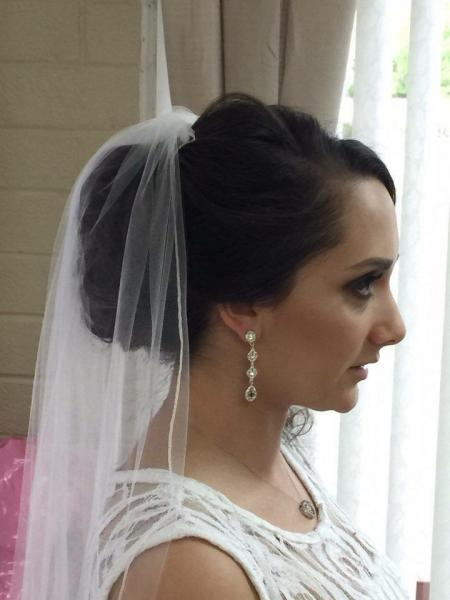 [Image: Reflections Hair Salon specializes in making brides look glamorous on their special day. This updo is styled around the bride's long veil for her special day!]